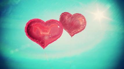 Heart balloons floating against blue sky