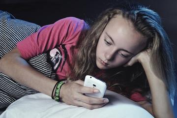 jeune fille dormant avec téléphone