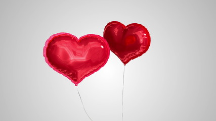 Heart balloons floating against grey background