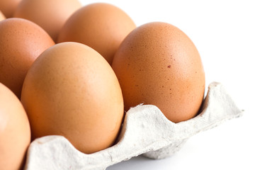 Corner of a tray of eggs on white background.