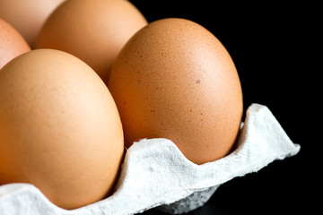 Corner of a tray of eggs on black background.