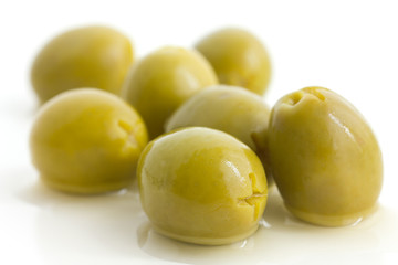 Pitted green olives with brine on white.