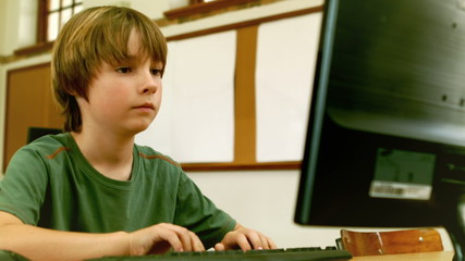 Cute little pupil looking at laptop in classroom