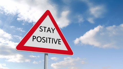 Stay positive road sign over cloudy sky