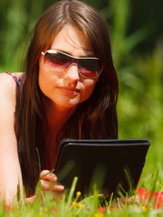 Woman using tablet computer reading outdoors.