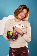 Beautiful woman holding white little Easter bunny basked eggs