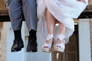 Detail of the feet of the groom and the bride sitting on a scaff