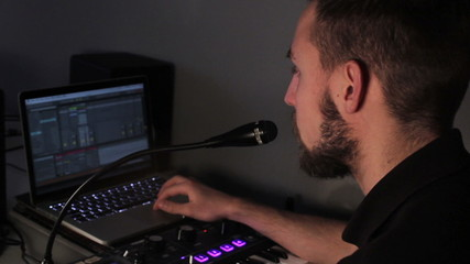 Man singing into a microphone in his home studio