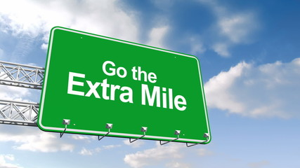 Go the extra mile sign against blue sky