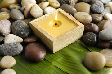 Handmade candle and pebbles on banana leaf