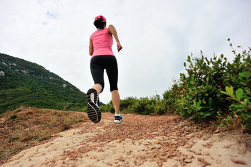 Runner athlete running on seaside mountain trail