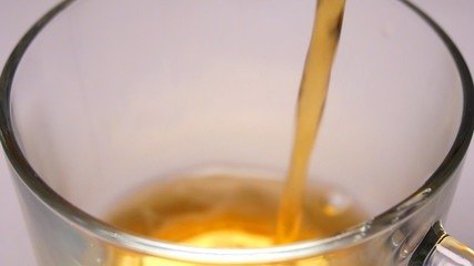 Pouring tea into the cup. Slow motion