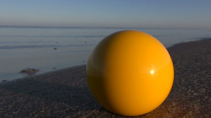 yellow billiards ball on summer sea resort beach