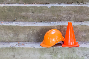 orange safety helmet and cone in construction site