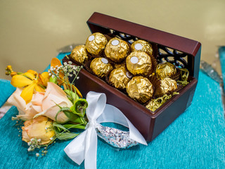 Chocolates in Gold Foil in a box on a velvet pillow as a wedding