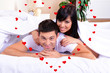 Beautiful loving couple lying in bed and heart-shaped frame