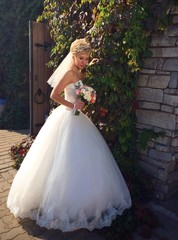 bride posing near stone wall with vine