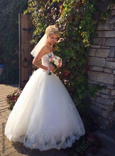 bride posing near stone wall with vine