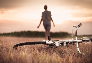 Woman and bicycle on a rural landscape