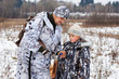 Leinwandbild Motiv hunter shows his son how to charge the gun