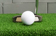 Putter address at golf ball on artificial grass.