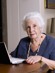 elderly woman, with a computer, looking at camera