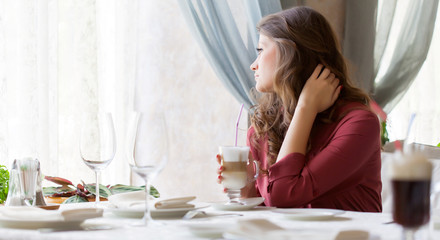 A woman in a restaurant is drinking coffee