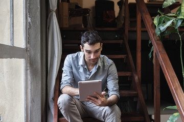 Young man using a tablet on the stairs in the office