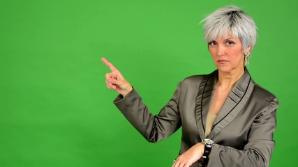 business woman points to watch - green screen
