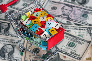 Shopping cart with question marks on dollars banknotes