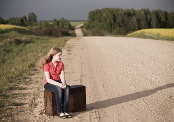 sad girl on road with vintage suitcases