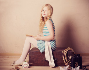 girl reading book on suitcase indoor