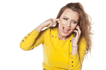 young woman posing trying to talk by phone in a loud environment