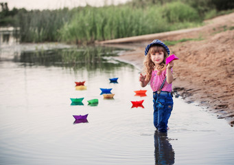 smile child playing with paper boats in a river