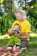 Young grandmother gives water to her little grandson