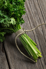 Close up of fresh tied parsley on wooden table.