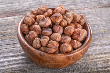 domestic hazelnuts in a wooden bowl on old rustic table