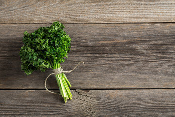 Fresh parsley on wooden table.