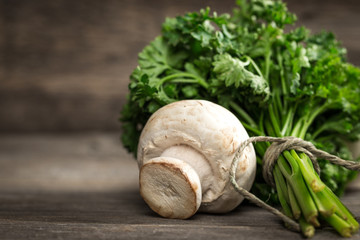 Fresh parsley with white mushrooms. On wooden surface