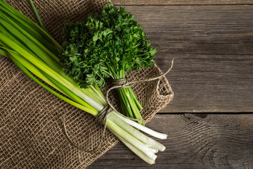 Fresh green onion with parsley on burlap sack. On wooden table.