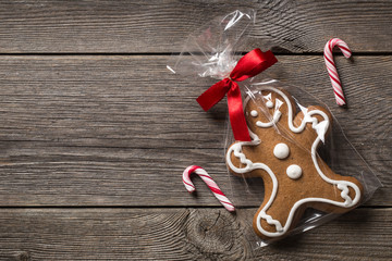 Packed gingerbread cookie on wooden background with candy canes