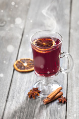 Hot mulled wine in a glass with spices on wooden table.
