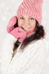 Cute young woman in winter outfit with snowflakes background.