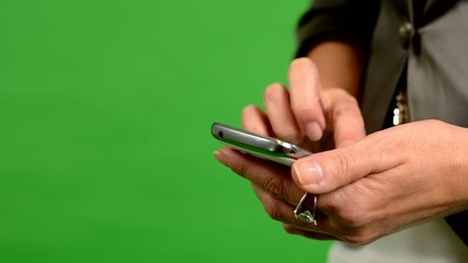 business woman works on phone - green screen - studio - closeup