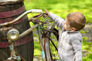 2 years old curious boy walking around the old bike