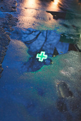 green cross of drugstore reflected in rain puddle