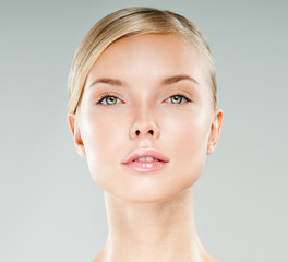 Beautiful face of young adult woman with clean fresh skin. Looki