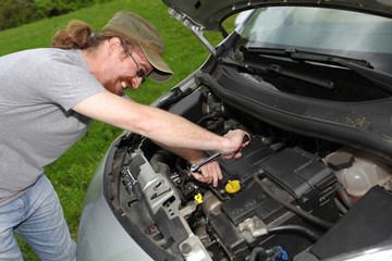 mechanic repairs a car on the road