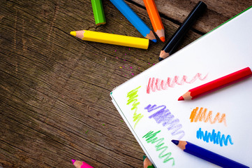 Bright pencils on wooden background