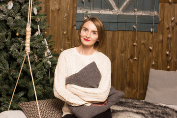 beautiful girl sitting on a couch in a Christmas interior